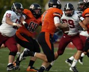 Lawrence High's Matt Weiss (69) and Kieran Severa (39) bust through the Shawnee Mission offense as they chase down SMNW quarterback Lucas Karlin in the first half action, Friday, Sept. 7, 2012, in Overland Park.