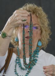 "Kathy Morgan, of Morganton, N.C., picks out a turquoise necklace to purchase. ""I came a long way just for this,"" said Morgan of her trip to the annual market."