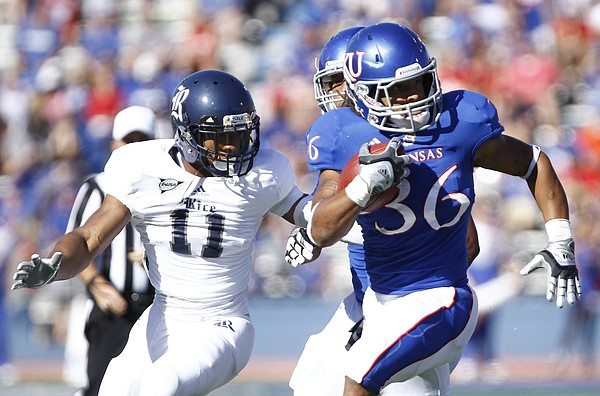 Kansas running back Taylor Cox is tailed by Rice cornerback Malcolm Hill during the third quarter on Saturday, Sept. 8, 2012 at Memorial Stadium.