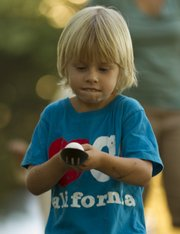 Henry Gottsfield, 5, of Lawrence, concentrates on keeping his spoon steady as he takes part in an egg-and-spoon race during the picnic Saturday.