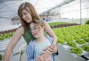 "Caroline Eddinger and her daughter Stella, 10, help operate Two Sisters Farm where a hydroponic greenhouse system is used to grow several varieties of lettuce. They sell ""living lettuce"" to several Lawrence area grocers and restaurants."