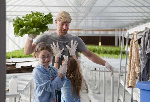Ryan Eddinger, Lecompton, greets his daughters Stella 10, left, and Sophia, 8, after harvesting some lettuce at their Two Sisters Farm grown with a hydroponic greenhouse system and producing several varieties of lettuce. Their products are used in several Lawrence restaurants and area grocers.