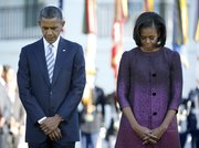 President Barack Obama and first lady Michelle Obama, joined by members of the White House staff pause during a moment of silence to mark the 11th anniversary of the Sept, 11th, Tuesday, Sept. 11, 2012, on the South Lawn of the White House in Washington.
