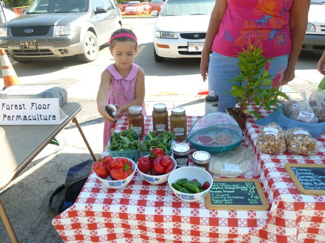 A young farmer-in-training helps keep produce fresh for The Yeast We Can Do patrons at Cottin's Hardware Farmers Market.