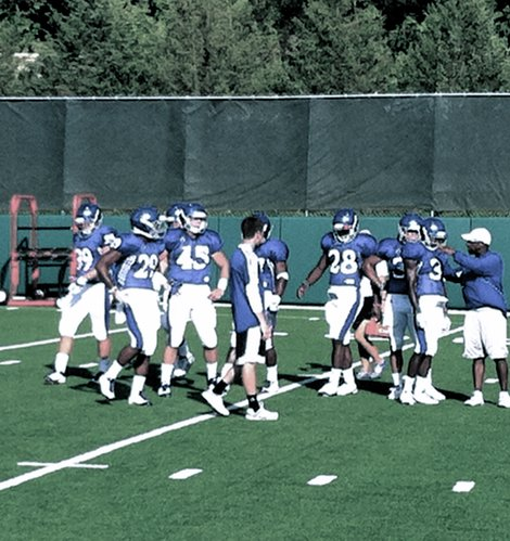The KU running backs take instructions from assistant coach Reggie Mitchell at the outset of a blocking drill at Wednesday's practice.