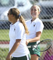 Free State sophomore Megan McReynolds, back, has a laugh with junior Alexis Czapinski during a doubles match between against Mill Valley's Sarah Wetzel and Mikaela McCabe on Wednesday, Sept. 12, 2012, at Free State High School.