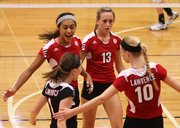 Lawrence High players, clockwise from top left, Caitlin Broadwell, Caroline Dykes, Monica Howard and Zoe Reed celebrate a point against Leavenworth during the second set on Thursday, Sept. 13, 2012 at Lawrence High School.