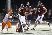 Lawrence High quarterback Brad Strauss looks to break free of the Olathe East defense during a run in the third quarter on Friday, Sept. 14, 2012 at Lawrence High School. At left is Olathe East linebacker Trenton Clark.