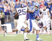 Kansas running back Taylor Cox puts a stiff arm on TCU cornerback Kevin White during the first quarter, Saturday, Sept. 15, 2012 at Memorial Stadium.