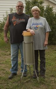 Leo and Nancy Pollard stand next to their 8-inch rain gauge in Lecompton, where for 30 years they have been gathering weather data for the National Weather Service in Topeka.