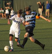Free State senior forward Caleb Francis (13) tries to hold off Shawnee Mission East defender Jack Sernett as the two struggle to gain control of the ball during the first half of Free State's soccer match against Shawnee Mission East, Tuesday, Sept. 18, 2012 at FSHS.