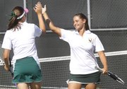 Caitlin Dodd, left, and Emily Sadosky celebrate a point during a Free State quad tennis meet Wednesday, Sept. 19, 2012, at FSHS.