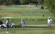 A golfer chips onto a green Wednesday at Lawrence Country Club, as a club employee waters a green in the background. The club has started charging its members a special assessment to help pay its water bill.