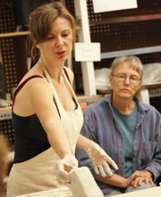 Ceramist Monika Laskowska passes a sample of clay around to students in her class Tuesday at the arts center. At right is her student and Lawrence resident Jean Burgess.