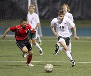 Free State midfielder A.J. Ware chases down the ball with Shawnee Mission North defender Colin Dujakovich during the second half on Thursday, Sept. 20, 2012 at Free State High School.