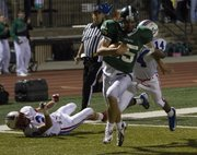 Free State&#39;s Kyle McFarland avoids tackle attempts by Olathe North&#39;s Jake Reed (2) and Jeighlon Cornell (14) as he runs into the end zone for a score during their game Friday, Sept. 21, 2012, at FSHS.