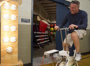 Derrick Abromeit, of Lawrence, pedals a modified exercise bike in order to light up lightbulbs in a demonstration put on by Bowersock Hydroelectric to show how much more energy it takes to power an incandescent bulb than a compact fluorescent lightbulb during the Lawrence Energy Conservation Fair held Saturday at Holcom Park.