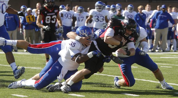 Toben Opurum, (35) Anthony McDonald (51) and Ben Heeney (31) bring down Huskies quarterback Jordan Lynch (6) in the first half of KU's game against the Northern Illinois on Saturday at Huskie Stadium in DeKalb, Ill.
