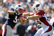Former New England Patriots linebacker Mike Rivera, left, fights through a block by Arizona Cardinals running back Anthony Sherman during their game on Sept. 16, 2012, in Foxborough, Mass.