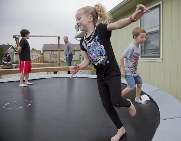 Claire Arnold, 8, center, and her brother Zach, 6, right, play on their families trampoline at their Eudora home. Both children have been diagnosed with cystic fibosis, a chronic lung disorder.