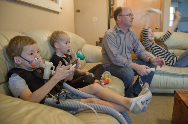 Zach Arnold, 6, left, and his sister Claire, 8, play a Super Mario Wii game and do their breathing treatments Monday, Sept. 24, 2012, at their Eudora home. The sibliings have been diagnosed with cystic fibrosis, a chronic lung disorder. At left is their father Bobby Arnold, Eudora, and their sister Madison, 12. The family will participate in a Great Strides walk Saturday in Lawrence to benefit the Heart of America Chapter of the Cystic Fibrosis Foundation.