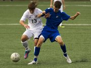 Free State forward Caleb Francis (13) and Leavenworth's Evan Lott get tangled up as they fight for control of the ball during Free State's soccer match against Leavenworth Thursday, Sept. 27, 2012 at FSHS.
