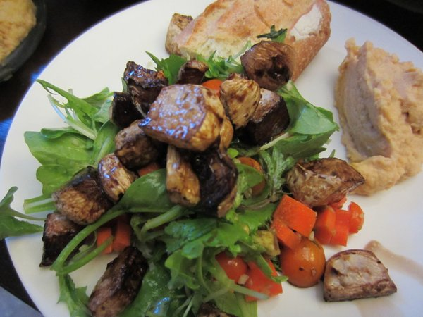 CSA salad topped with roasted turnips with a side of bread and homemade hummus.