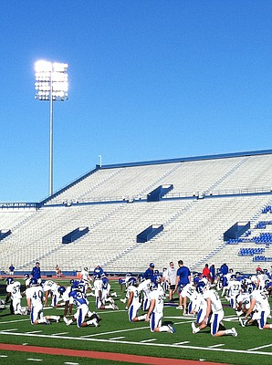 KU coach Charlie Weis (center right, gray hoodie) keeps his eye on the Jayhawks during stretching drills on Wednesday.