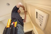 Rueschhoff Security technician Chad Greeson installs a motion-detecting devise above a security keypad inside a west Lawrence home on Thursday, Oct. 4, 2012. Representatives from Rueschhoff say that they have seen more business since early summer when Lawrence police began reporting a rise in home burglaries.