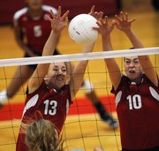 Lawrence High's Caroline Dykes, left, Monica Howard team up for a block against Shawnee Mission East on Thursday, Oct. 4, 2012, at LHS.