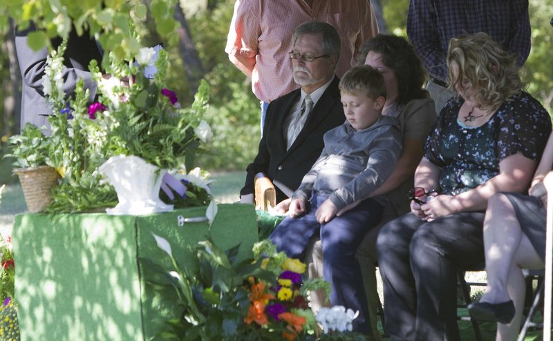 Michael Rutz, of Enterprise, left, attends the graveside services Wednesday, Oct. 3, 2012, for his son, Daniel Rutz, who died at age 28 after battling mental illness for years. Sitting next to Rutz, from left, are his wife, Renauda, who is holding Daniel's 7-year-old son Ryan, and Ryan's mother and Daniel's longtime girlfriend, Cassie Pemberton.