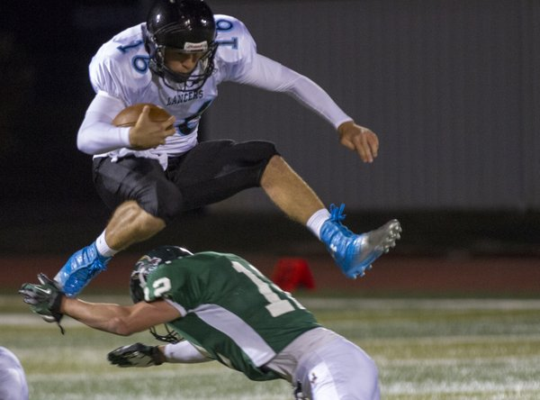 Shawnee Mission East quarterback Jordan Darling (16) hurdles Free State defensive back Joe Dineen during the Firebirds' homecoming game against the Lancers on Friday, Oct. 5, 2012, at FSHS.