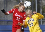 Kansas University forward Jamie Fletcher (11) heads the ball away from West Virginia's Kara Blosser during the Jayhawks' 1-0 loss to the Mountaineers on Friday, Oct. 5, at the Jayhawk Soccer Complex.