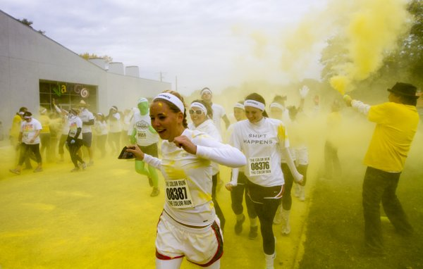 Volunteers spray runners with yellow chalk dust at the first color station during the color run in downtown Lawrence Saturday, Oct. 6, 2012.