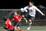Lawrence High forward Robert Lyan elevates to control the ball over Shawnee Mission North defender Colin Dujakovich during the first half on Tuesday, Oct. 9, 2012 at Lawrence High School.