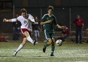 Lawrence High midfielder Justin Riley (21) launches a shot past Free State defender Jordan Patrick during their soccer match Thursday, Oct. 11, 2012 at LHS.