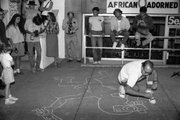 Artist and social activist Keith Haring draws on the sidewalk of Seventh Street in downtown Lawrence during the River City Reunion, which took place Sept. 7-13, 1987. The event brought together beat generation writers, punk bands and social activists.