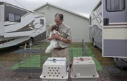 "Ric Wyrens, Lincoln, Neb., moves his Papillon dog ""Icey"" from their big motor home to their animal carrier to take them to competition at the Lawrence Jayhawk Kennel Club all-breed dog show Saturday, Oct. 13, 2012, at the Douglas County Fairgrounds. The event continues today."