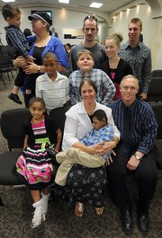 Janice Meyer, seated at center, and her husband, Gary, right, are pictured with their family at the Calvary Apostolic Church in Salina after receiving the Angels in Adoption Award in this Sept. 6 photo. For their involvement as foster and adoptive parents, the Meyers received the award, which is sponsored by the Congressional Coalition on Adoption Institute. The Meyers were among recipients who last month attended an official ceremony in Washington, D.C.