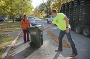 Lawrence resident Jessica Houk, left, gets her new 65-gallon city residential trash cart delivered on Monday by Tyler Green, an employee with Buckeye Diamond Logistics, which was contracted by the city to deliver the new containers. Crews delivered about 1,000 green plastic trash carts to the curbs of Lawrence residences Monday, and another approximately 19,000 are on the way as part of the city's program to require residents to use city-issued trash carts instead of cans or bags.