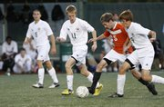 Free State soccer players Evan Smith (11), left, and Alex Heath (9) defend against Shawnee Mission Northwest's Tanner Sherman (5) in a 3-0 Firebirds loss on Tuesday, Oct. 16, 2012, at FSHS.
