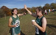 Free State's Sarah Lieberman, left, high fives teammate Sarah Schaffer after Schaffer finished the C-team 4K of the Sunflower League championships on Monday, Oct. 15, 2012, at Rim Rock Farm. Schaffer, a senior and three-year Firebirds runner who has Down syndrome, ran her final race Monday.