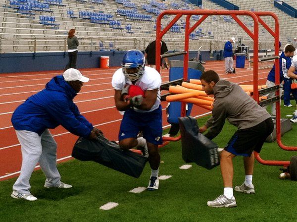 KU tailback James Sims takes a beating during a running back drill at Wednesday's practice.