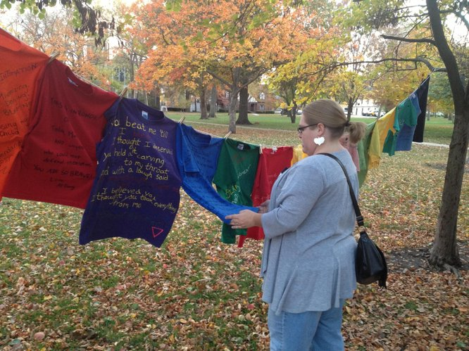 "Shannon Reid, a volunteer advocate for GaDuGi SafeCenter views shirts that are part of the ""Clothesline Project"" on display at Together Strong, Wednesday Oct. 17 in South Park."