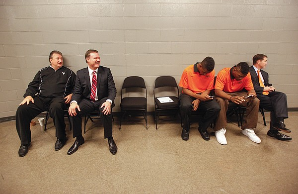 Kansas head coach Bill Self laughs with West Virginia head coach Bob Huggins while Oklahoma State head coach Travis Ford and his players, Le'Bryan Nash, left, and Marcus Smart await a television interview during Big 12 Media Day on Wednesday, Oct. 17, 2012 at the Sprint Center in Kansas City, Mo. Coaches and players representing each school in the conference were available for interviews.