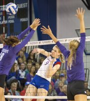 Kansas' Caroline Jarmoc (9) hits a shot down the line, avoiding a pair of Kansas State blockers during their volleyball match Wednesday, Oct. 17, 2012, at Horejsi Center.
