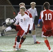 Johannes Reiber (12) settles the ball for Lawrence High School during the Lions' home game against Shawnee Heights, Thursday, Oct. 18.