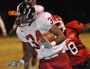 Lawrence High&#39;s Tyrone Jenkins (34) fights for extra yards in the first half against Wyandotte on Friday, Oct. 19, 2012, in Kansas City, Kan.