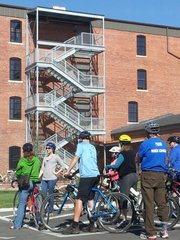 Abby Pierron, second from left, shows a group on a bike tour the Poehler Loft Apartments  at 619 E. 8th. The apartments were built from a former grocery warehouse, one example of East Lawrence's industrial past.
