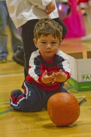 Rolling his pumpkin, Reed Agnelli, 2, was part of the fun during Family Fun Fall Festival at Woodlawn School, 508 Elm. Lawrence public school district leaves the decision to the schools whether to put on Halloween activities. Some schools do, while others have alternative celebrations this time of year.